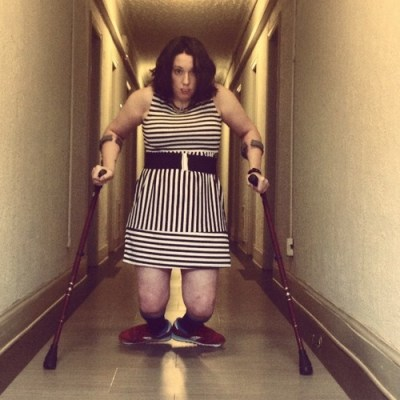 Illum walking down a hall with crutches