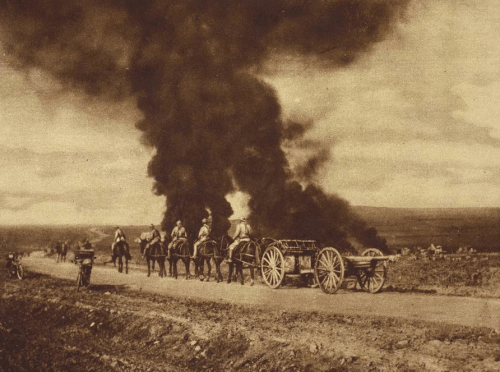 British artillery troops passing village bombed by enemy aircraft