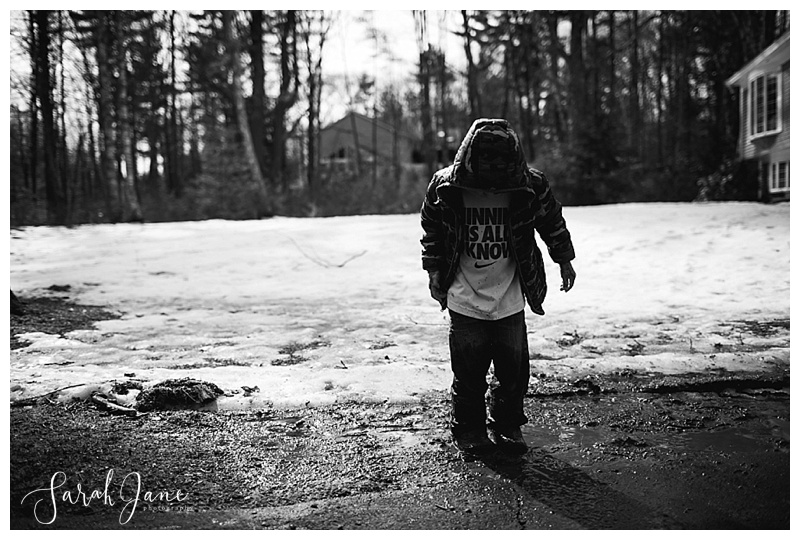 kid playing in the mud in spring in Maine