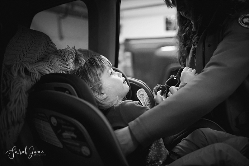 Child being buckled into car seat Sarah Jane Photography
