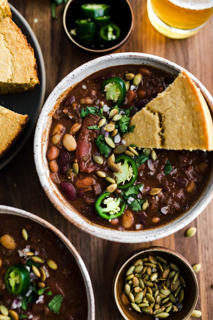Overhead close-up view of vegan chili with cornbread and jalapenos