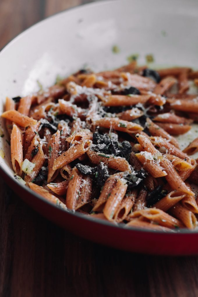 Side-angle photograph of red lentil pasta with black olives and parmesan.