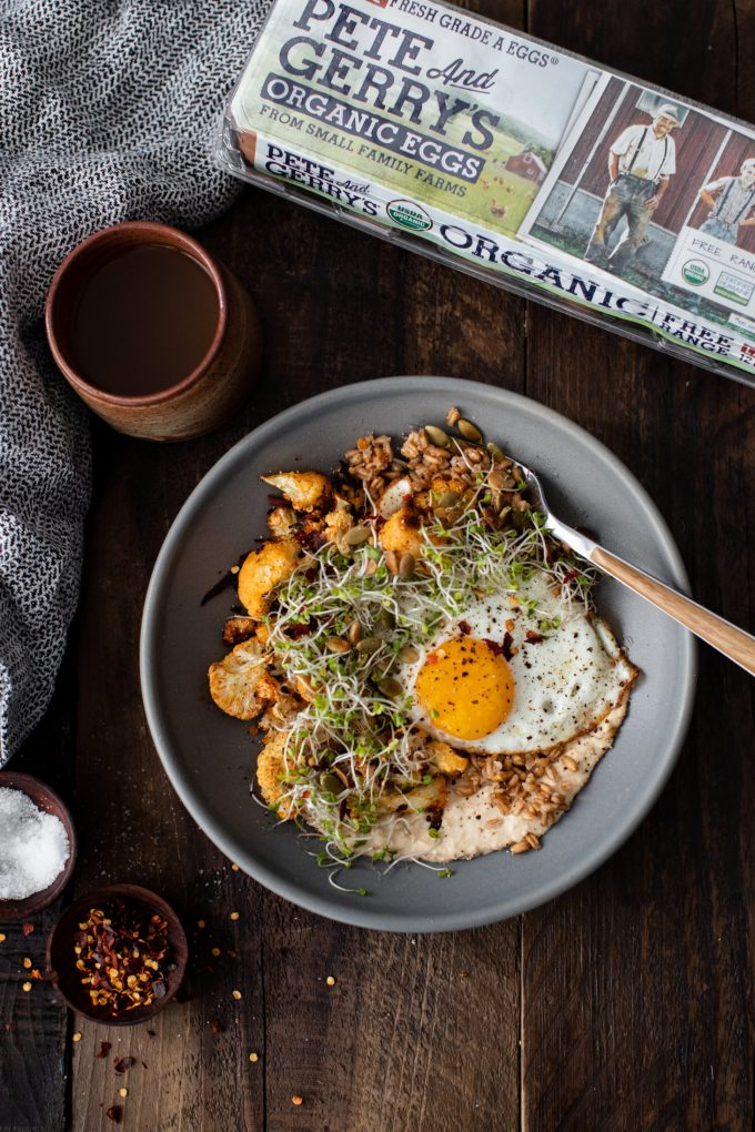 Overhead photograph of a cup of coffee and grey bowl with grains and a fried egg.