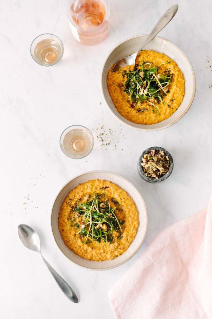 Overhead photograph of two bowls of Creamy Vegan Carrot Risotto Topped with Pea Shoots and Dill Hazelnuts.