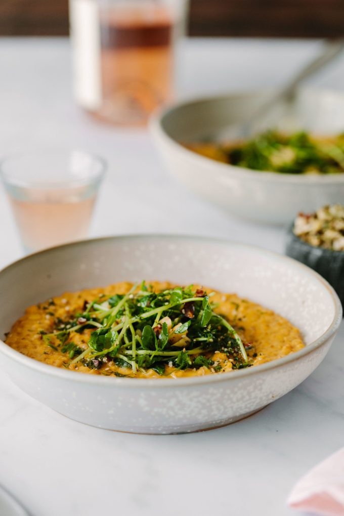 Side-angle of Vegan Carrot Risotto Topped with Pea Shoots and Dill Hazelnuts.