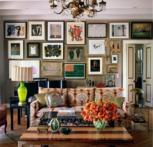 sala decorada no estilo boho chic, bohemiam chic com sofá estampado, quadros de vários estilos cobrindo toda a parede da sala, luminária com pase verde e cúpula listrada