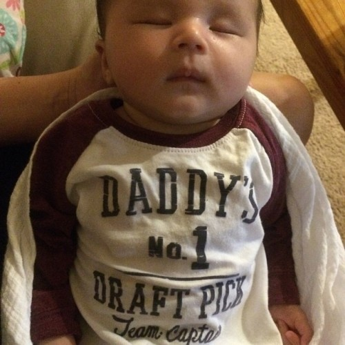 Ryan's fantasy football draft mascot is sleeping on the job.#pleasepickbetterthaninprioryears Also, I bought this in a size bigger than she is so she could wear it throughout football season. Can someone please tell me how my 8 week old is fitting into 6 month old clothing?