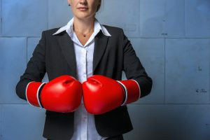business woman with red boxing gloves on,ready to battle, against an industrial background