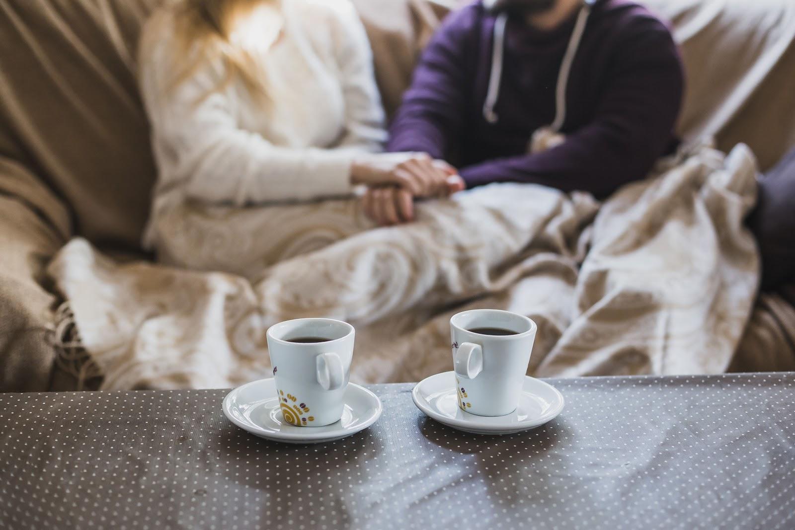 casal sentado com foco nas xicaras de cafe enfrente a eles