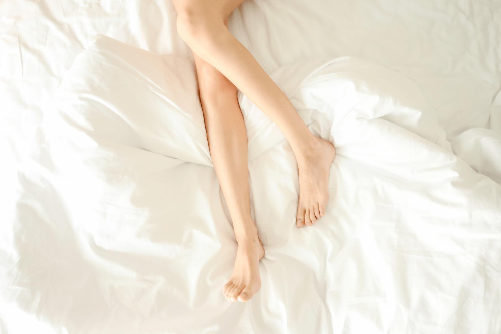 herpes genital pernas de uma mulher deitada na cama