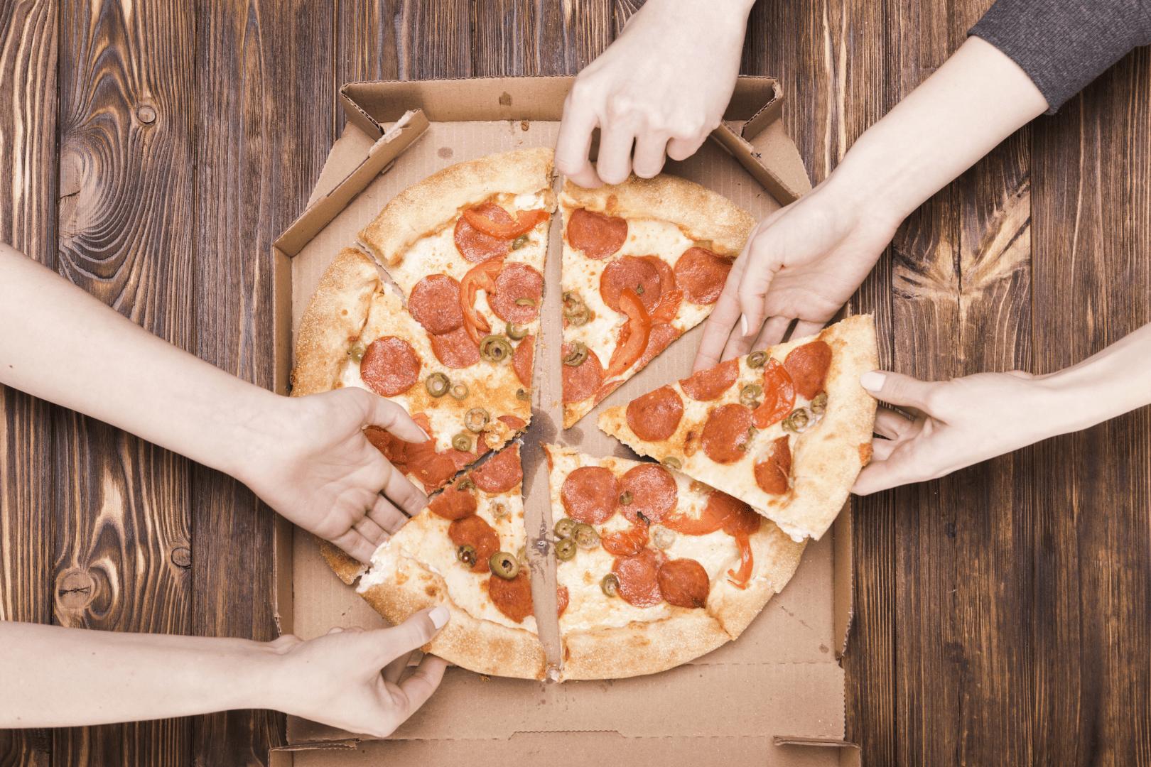 intoxicacao alimentar pessoas pegando um pedaço de pizza com as maos