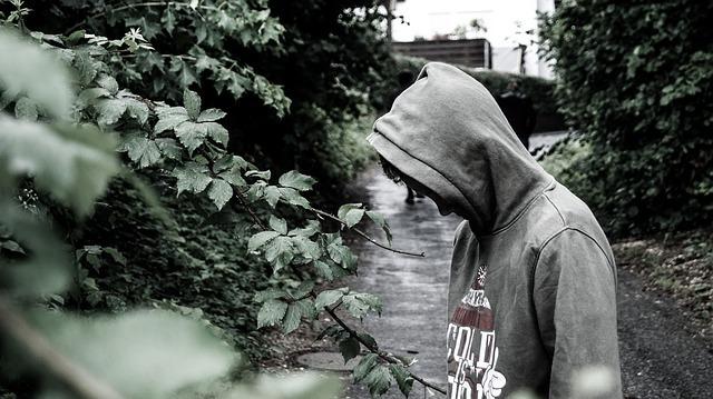 pessoa escondendo o rosto com um capuz
