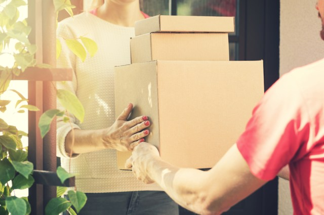 Woman accepting home delivery from courier