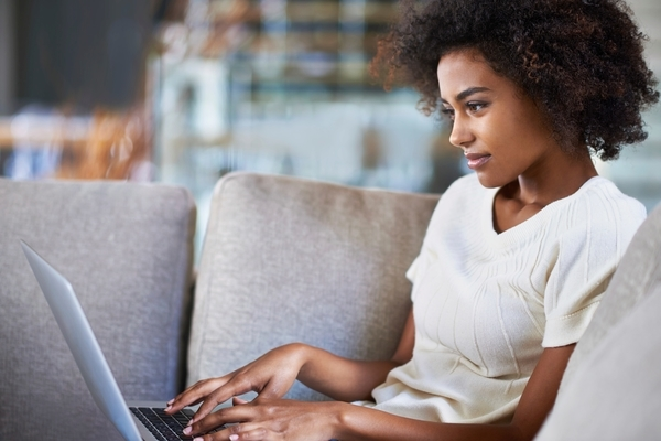 Woman on couch using laptop for improving customer experience through web self-service
