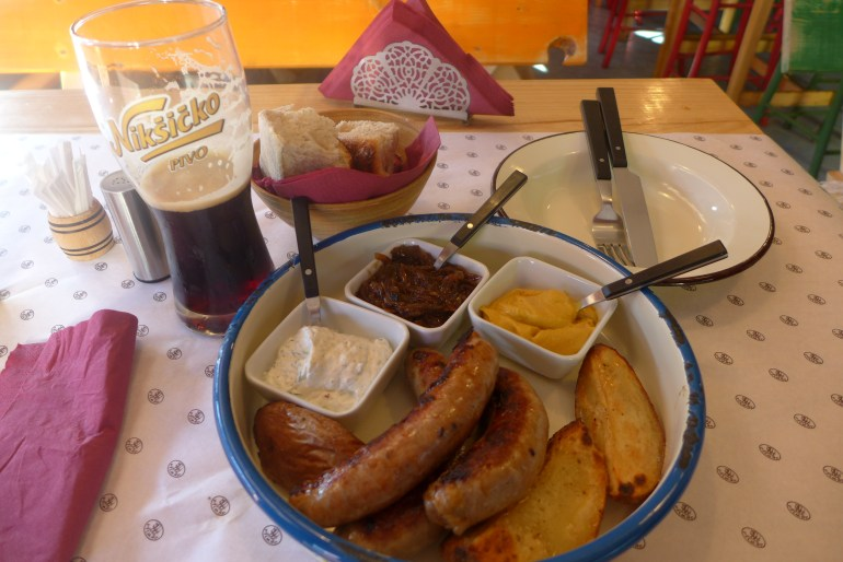 Three different types of sausages, served with potatoes, caramelized onions, a mustard sauce, and a yogurt sauce - and a Nikšićko Dark to wash it all down.