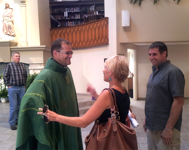 Father Chris greets a family  after Mass at St. Anne Church in Barrington, Photo courtesy of Karen McBride.