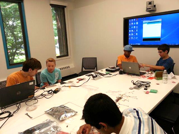Local teens working on Maker Camp projects in the Conference Room at the Barrington Area Library