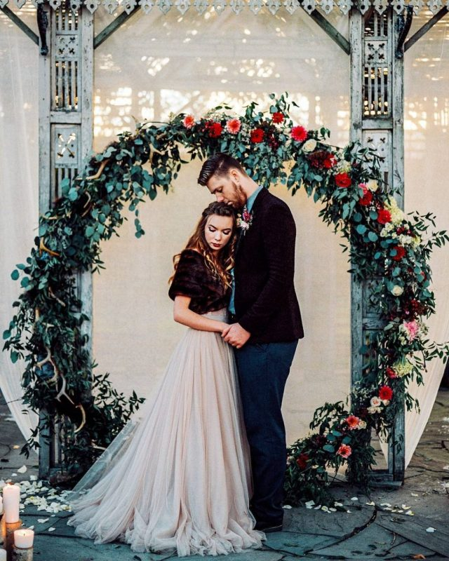 bride and groom in front of white wall, grey pillars, and large wreath of greenery, adorned on one side with red, pink, and white flowers, sitting on the ground
