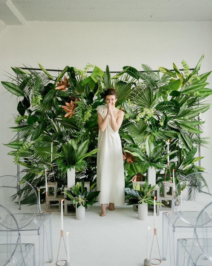 bride stands in front of lush backdrop of tropical greenery and flowers