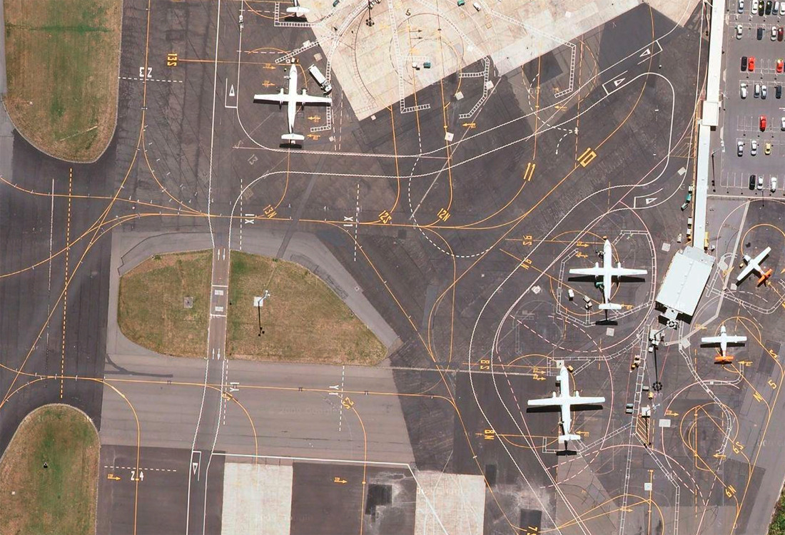 An airstrip near a terminal with many squiggly lines instructing the planes on where to go