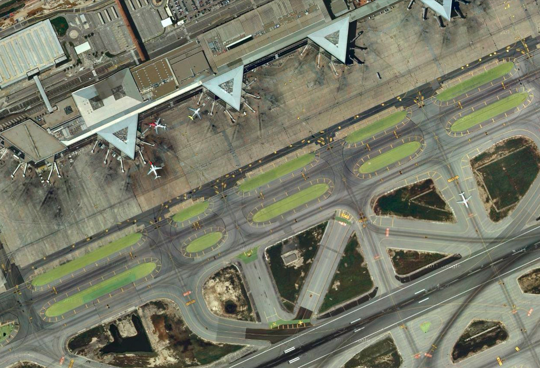 An aerial view of an airport showing planes parked at and driving towards the terminal