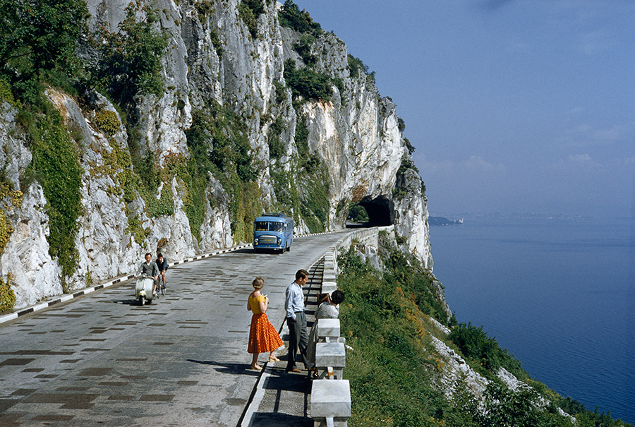 Motorists pass people on a scenic road atop a cliff overlooking a bay near Trieste, Italy, 1956.Photograph by B. Anthony Stewart, National Geographic Creative