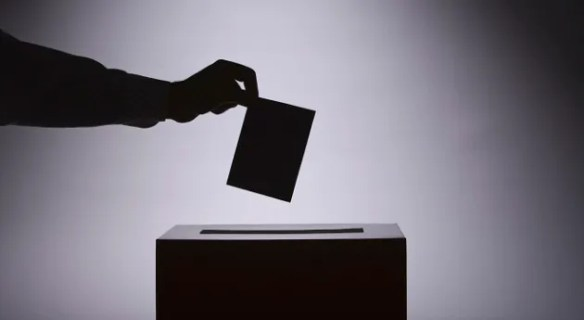 A silhouette of someone dropping a ballot into a ballot box
