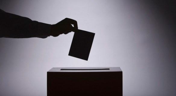A silhouette of someone dropping a ballot into a ballot box