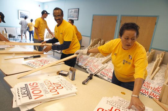 A photo of members of the United Food and Commercial Workers union assembling picket signs
