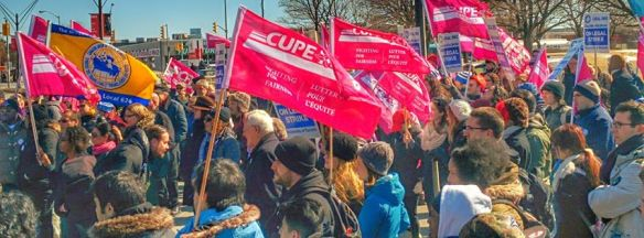 CUPE flags flutter above the crowd at a solidarity rally at the main gate picket line.