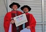 Two graduating members holding a #shameonshoukri sign at convocation.