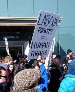 """A sign reads """"labour rights = human rights"""""""