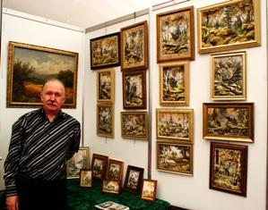 Анатолий Ничик на фоне своих работ