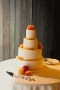 AS8-4-tier-cream-round-Indian-wedding-cake-with-orange-ribbon-and-flowers