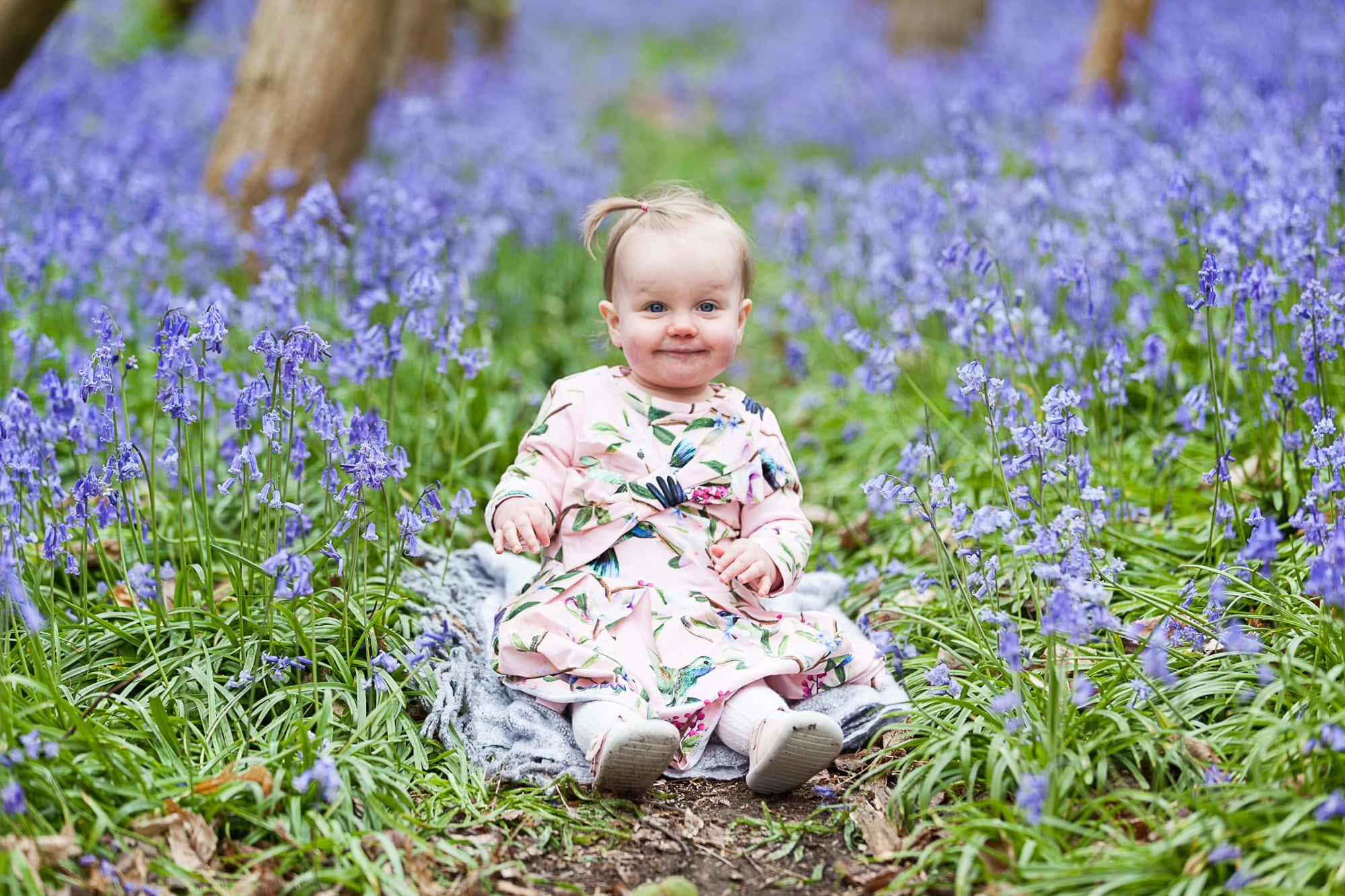 baby girl in ted baker dress sat in the bluebells at her Sevenoaks family bluebell shoot