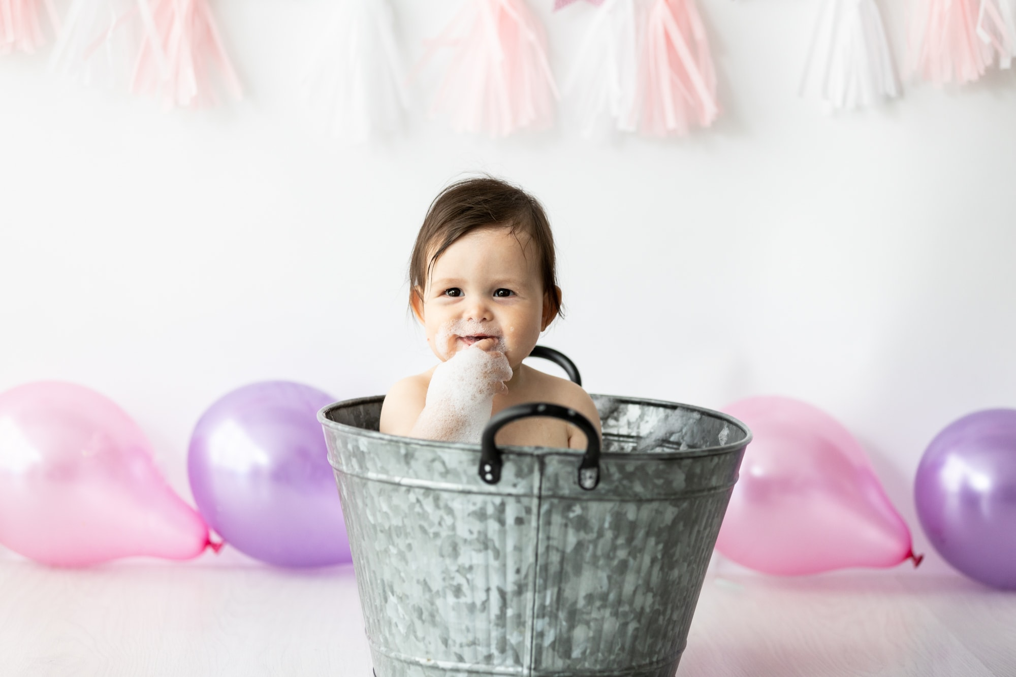 baby girl in tin bath on her first birthday cake smash photoshoot in bexley