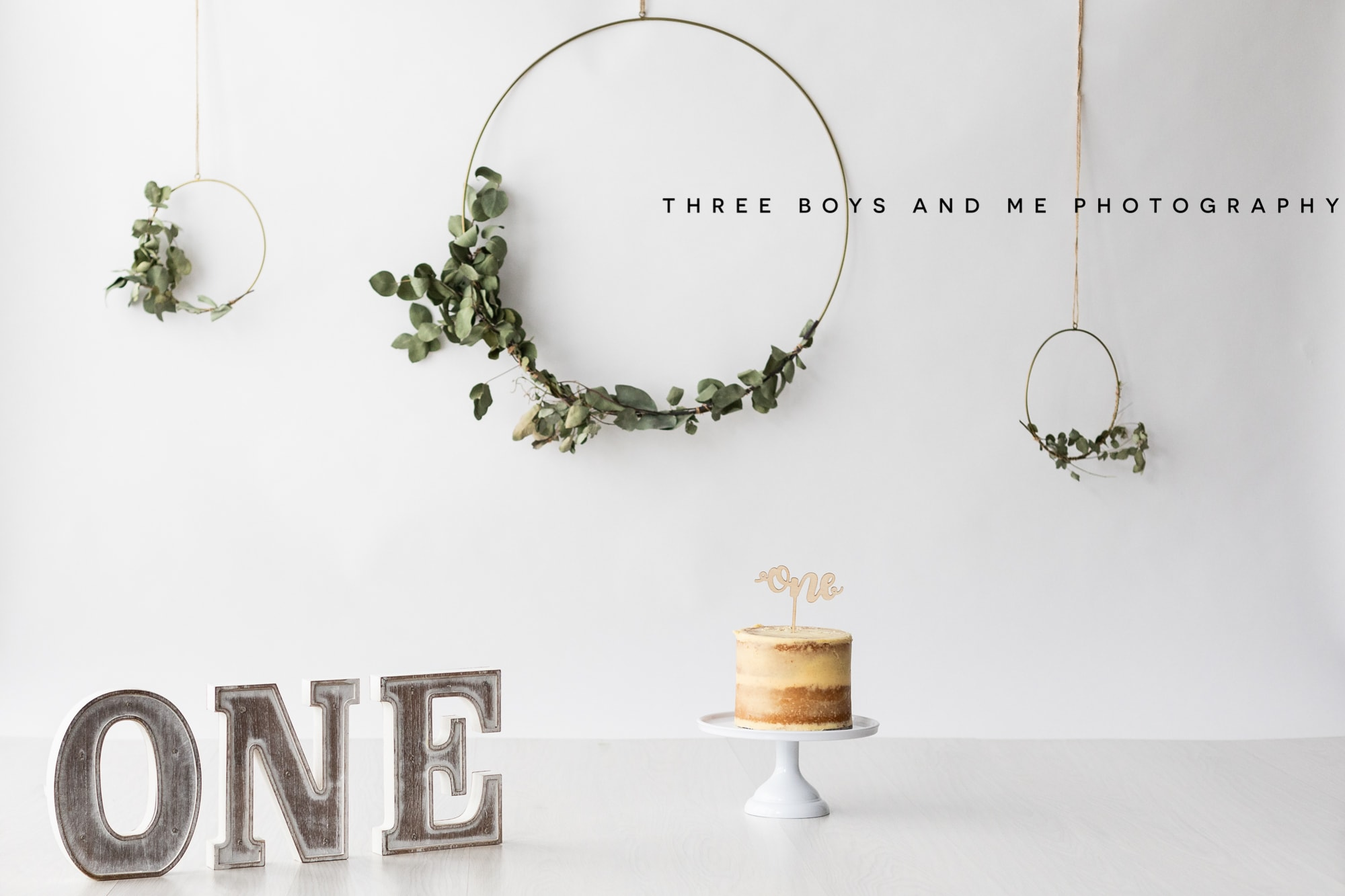 neutral cake smash set up with foliage brass hoops, nude cake with ONE sign at Bexley cakesmash photoshoot