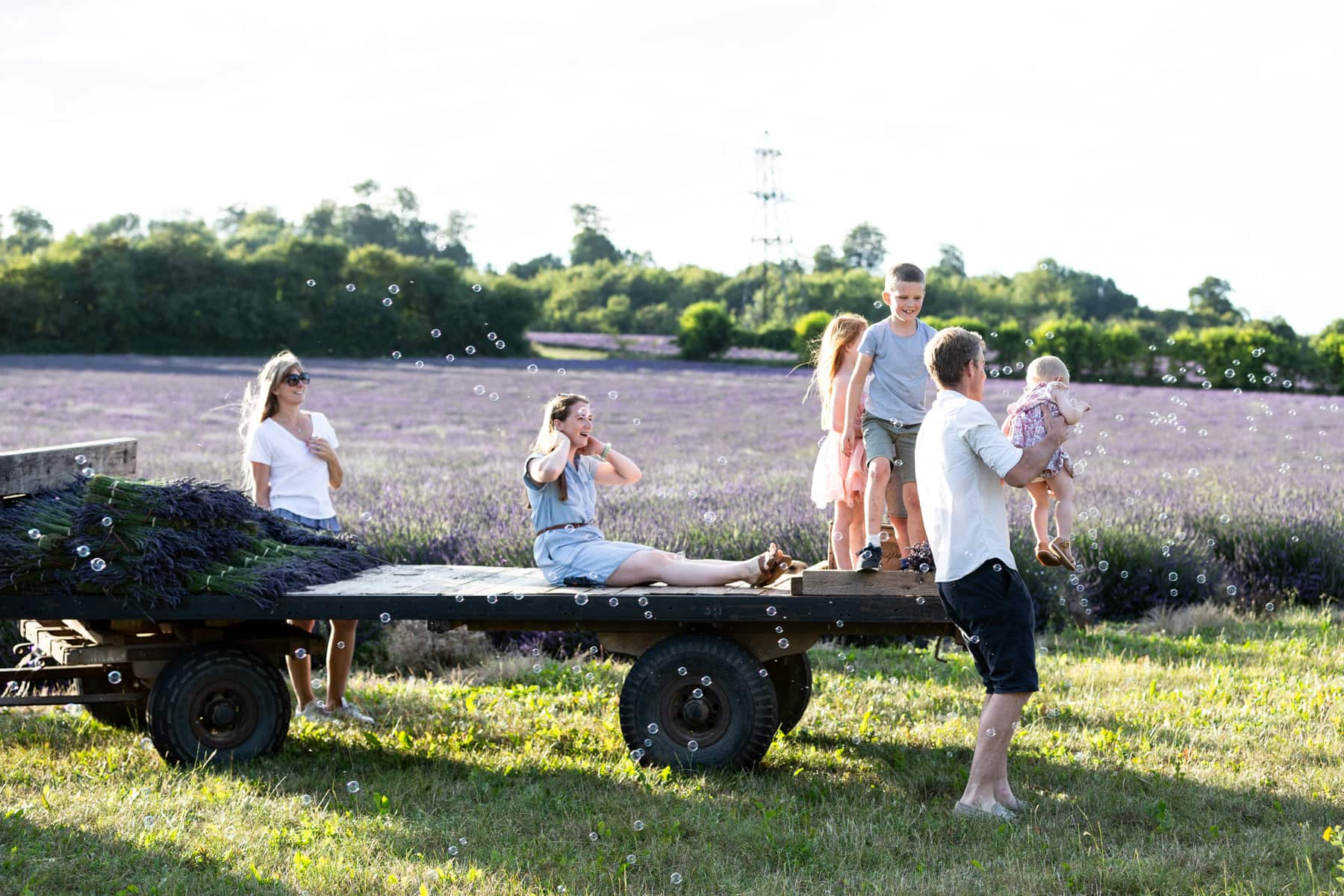 Children chasing bubbles sat on a tractor trailer at their lavender family photoshoot in Shoreham Kent
