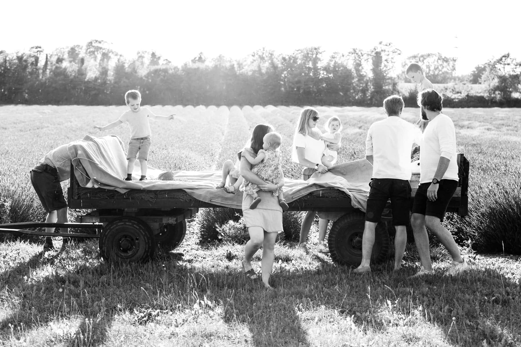 Extended family with small children on tractor trailer shot at a extended family photoshoot in the lavender fields at Castle farm Shoreham Kent