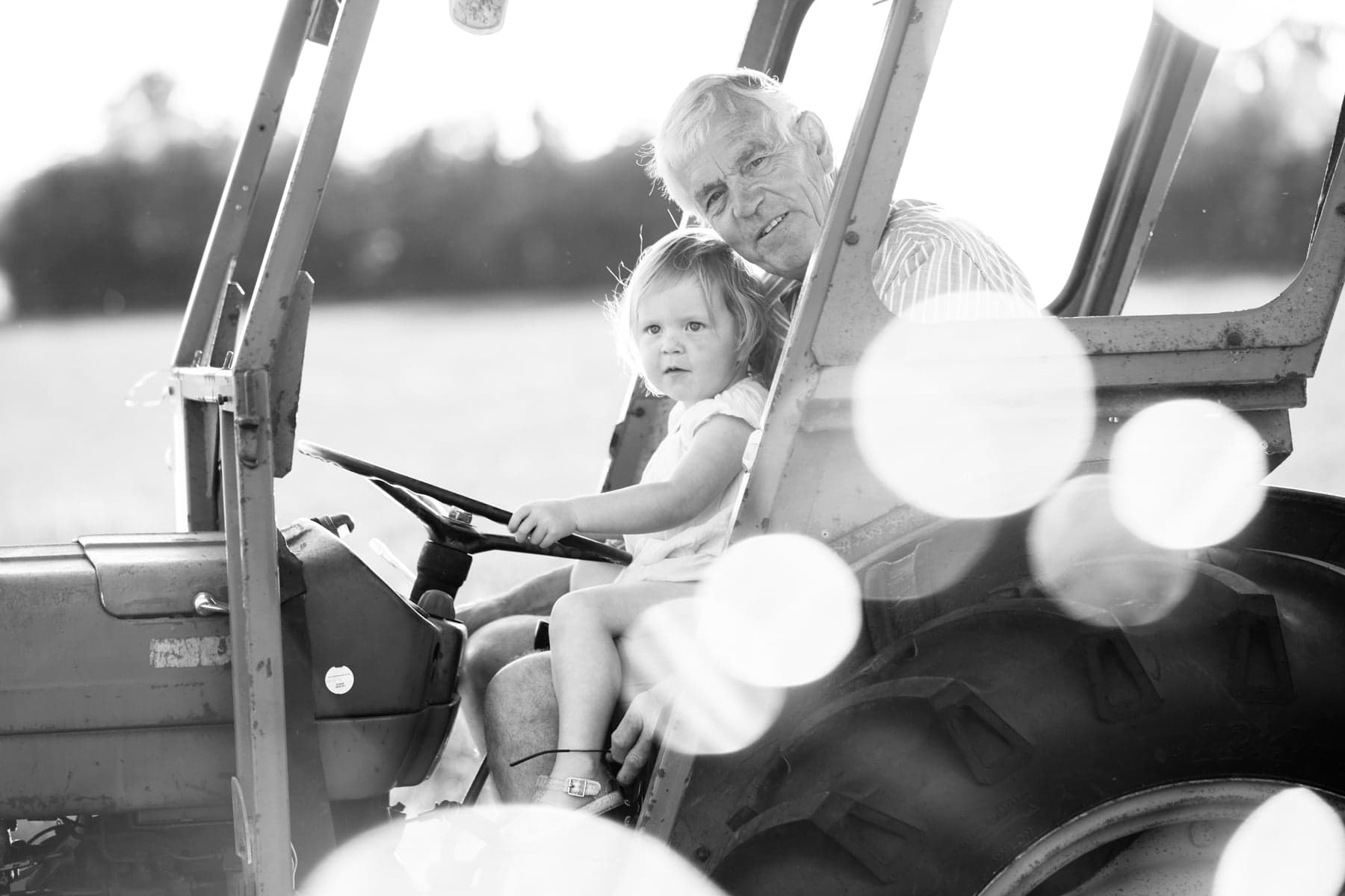 Grandad and Granddaughter sat in tractor black and white image shot in the lavender fields of shoreham