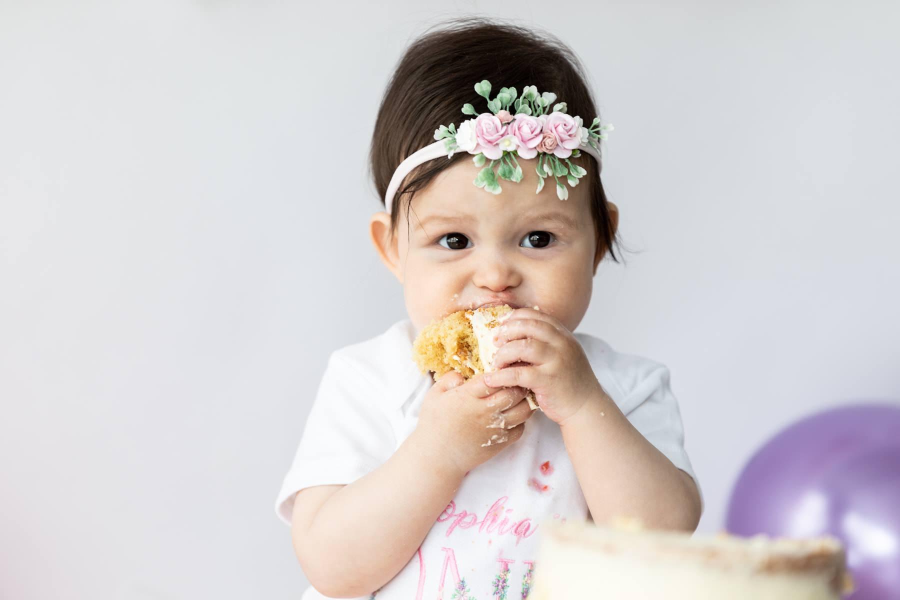 little girl wearing pink flower headband eating cake at her Kent cake smash photoshoot in Bexley