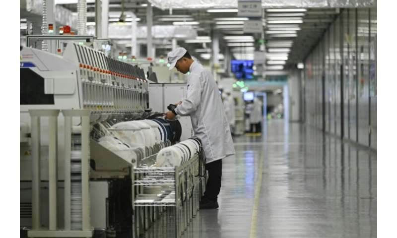 An employee works on a mobile phone production line at a Huawei production base during a media tour in Dongguan