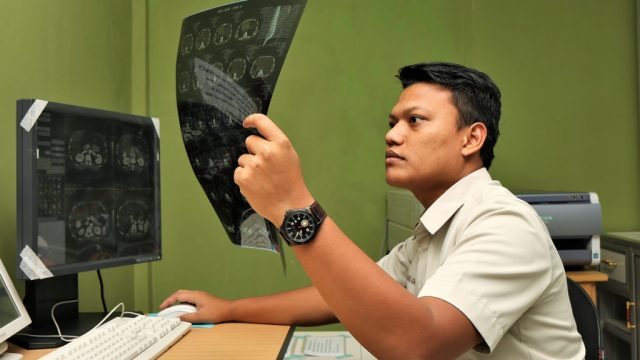 A radiology technician at Imanuel Baptist Hospital examines the CT scan of a patient. IMB photo