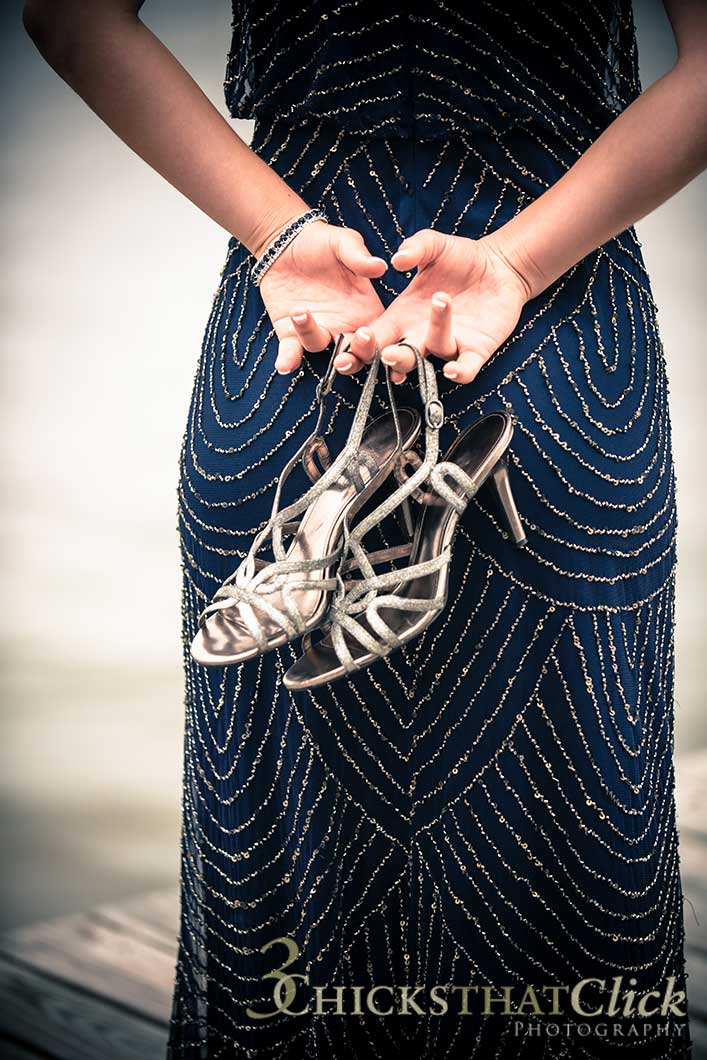 Young woman in prom dress holding shoes