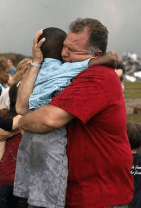 Oklahoma teacher embraces one of his surviving students pulled from the rubble.