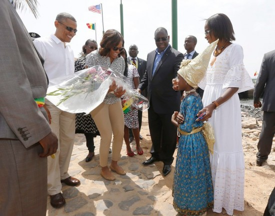 U.S. President Barack Obama and first lady Michelle Obama receive a bouquet as they arrive on Goree Island near Dakar