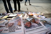 Newspapers with front pages depicting South Africa's former President Nelson Mandela are displayed at a vendor's stand in Ikoyi district in Lagos