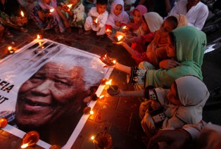 Children hold earthen lamps in tribute to former South African President Nelson Mandela, organised by Aafia Movement in Karachi