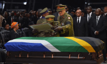 Tribute: A military officer places the framed flag of South Africa on top of Mandela's coffin at the start of his funeral service this morning