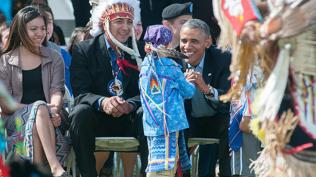 Barack Obama chats with a young dancer alongside Dave Archambault II, Standing Rock Sioux